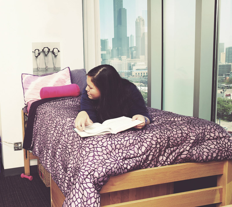 Female student studying on her bed with Chicago Skyline in background
