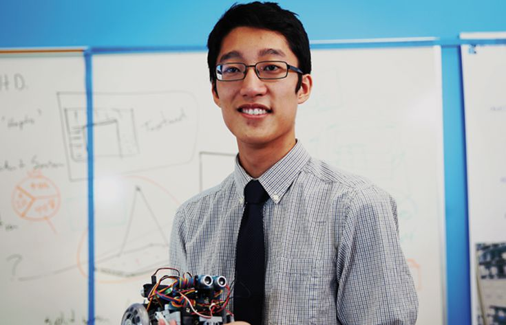 Male student with robot in Hand in front of Whiteboard